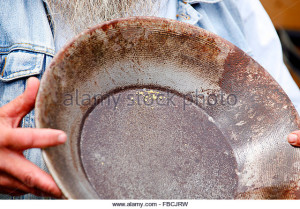 gold-dust-flakes-in-a-pan-demonstrated-by-a-gold-miner-in-the-eldorado-fbcjrw